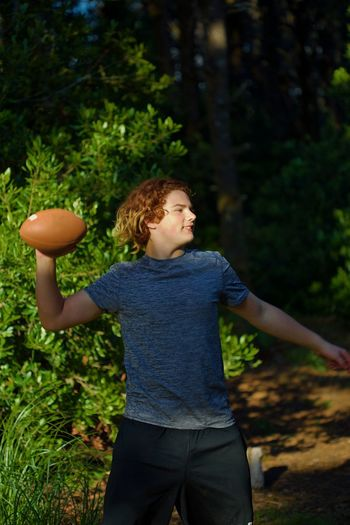 Young man throwing american football on field