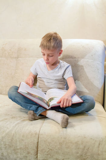 Full length of boy studying while sitting on sofa at home