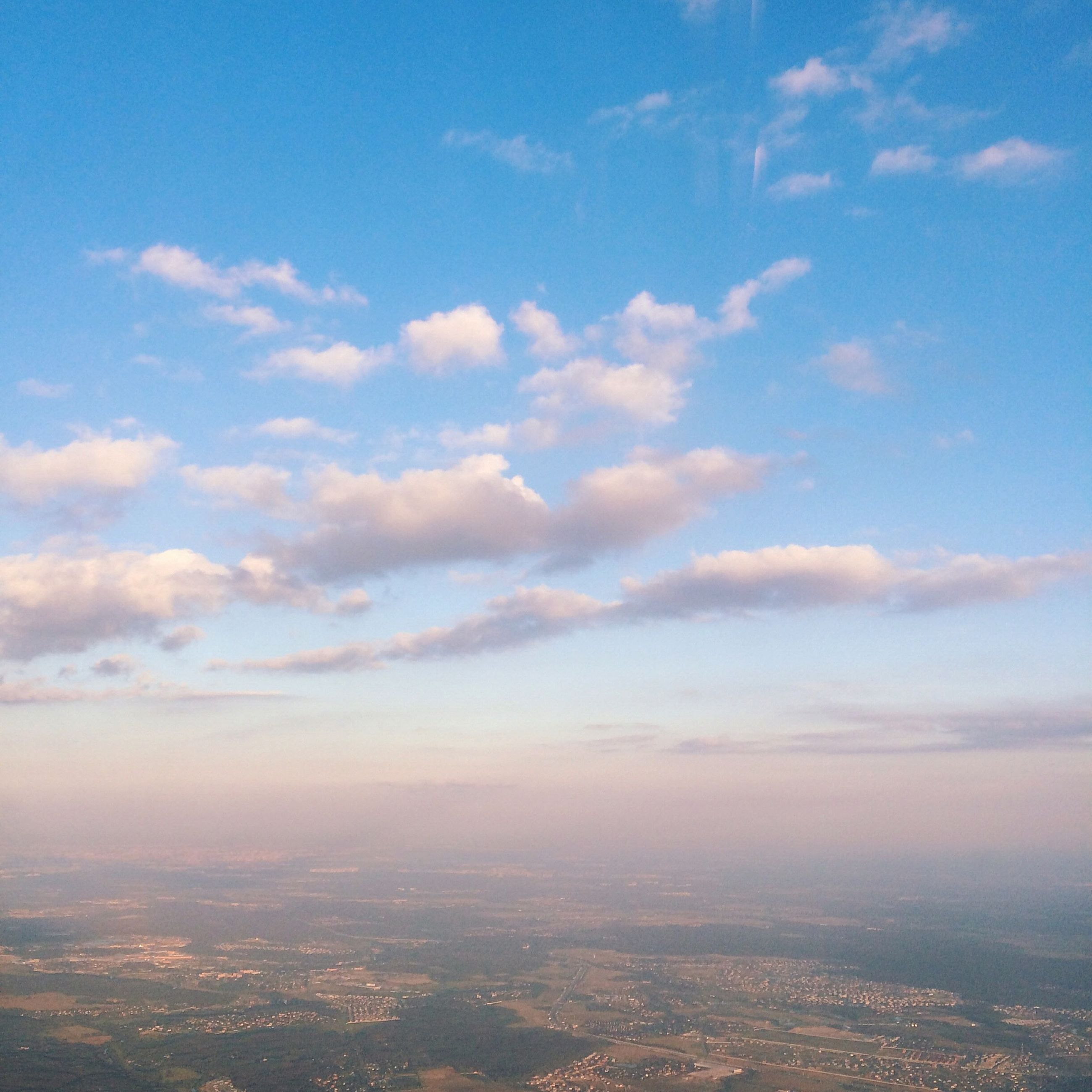 sky, aerial view, cloud - sky, blue, scenics, beauty in nature, tranquil scene, cloud, cityscape, nature, tranquility, landscape, city, outdoors, no people, idyllic, cloudscape, high angle view, day, horizon over land
