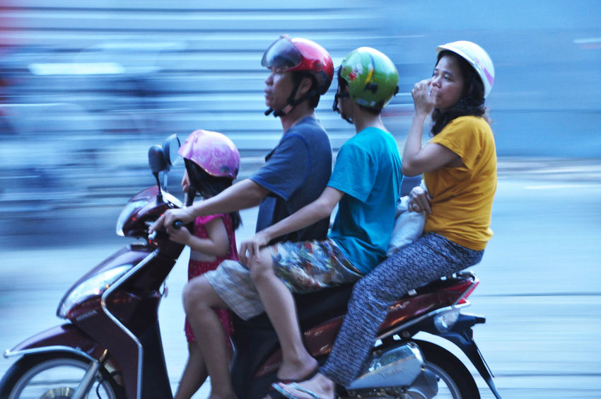 Family on evening outing in Hue, Vietnam. Boys Children Evening Families Family Helmets Hue Imperial City Motion Blur Motorbikes Motorcycles Motorscooters Outings  Parents Safety Speed Streets Toddlers  Transport Vietnam