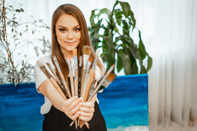 Portrait of smiling woman holding paintbrushes at home