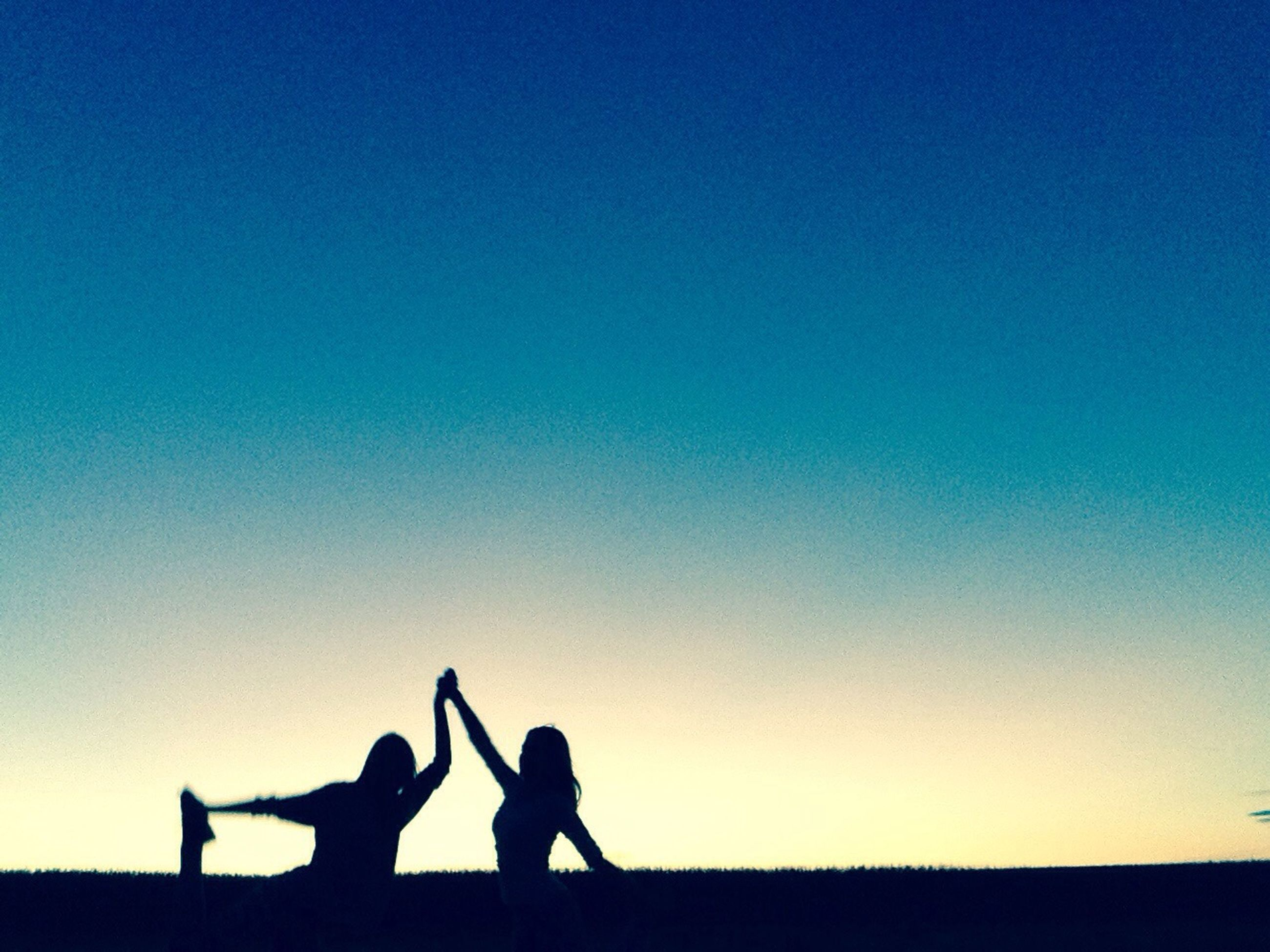 togetherness, lifestyles, silhouette, leisure activity, copy space, men, bonding, clear sky, love, friendship, sunset, person, blue, standing, childhood, sitting