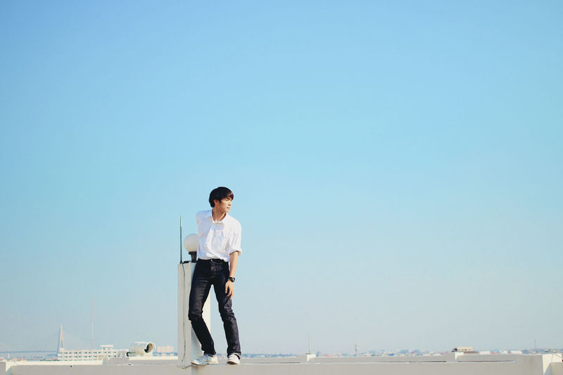 Full length of man standing on sea against clear sky