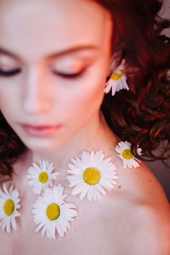 Close-up of beautiful young woman wearing flowers and make-up