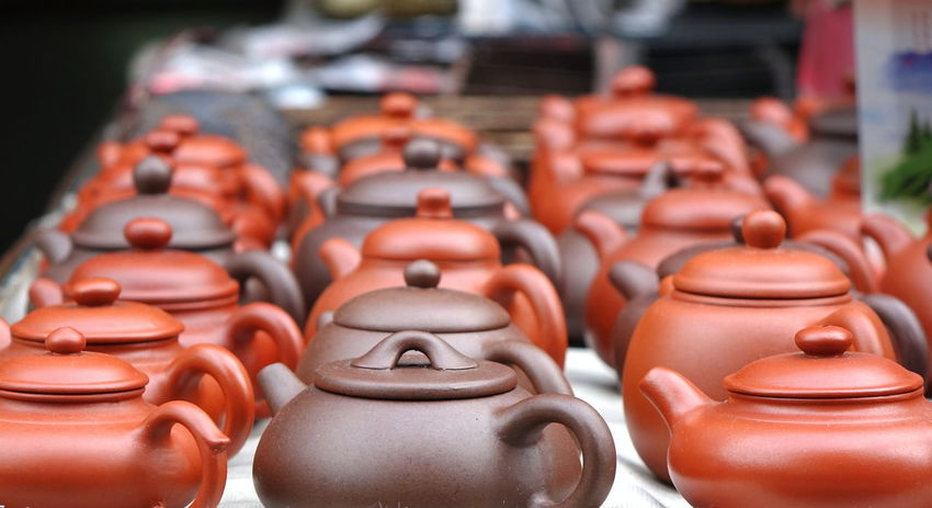 Traditional earthenware teapots are sold at an outdoor market Breakable  Tea Culture Art And Craft Brown Ceramics Chinese Culture Craft Earthenware Focus On Foreground For Sale Fragile In A Row Lid Pottery Teapot Traditional