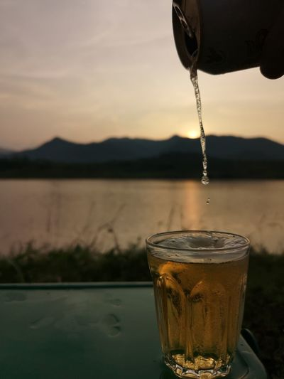 Close-up of beer glass against lake during sunset