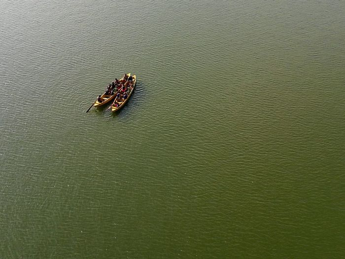 High Angle View Of People Boating In Green Water