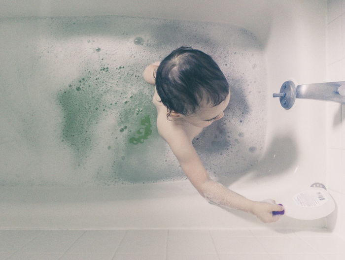 High angle view of girl in bathtub at home