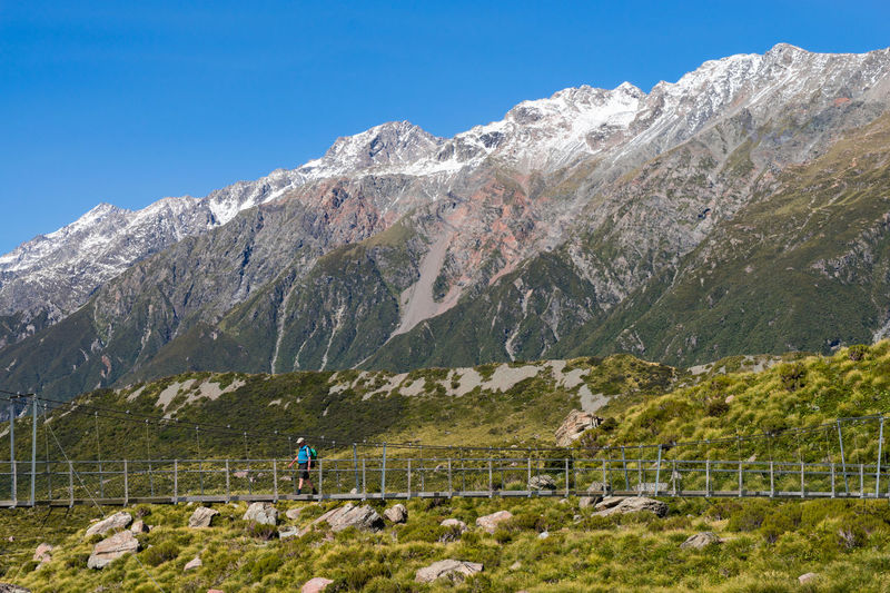 A lone hiker crosses a suspension bridge in Mount Cook National Park, New Zealand. Beauty In Nature Blue Clear Sky Cold Temperature Geology Landscape Men Mountain Mountain Range Nature Non-urban Scene Physical Geography Scenics Snow Snowcapped Mountain Tourism Tourist Tranquil Scene Tranquility Travel Travel Destinations Tree Unrecognizable Person Vacations Winter