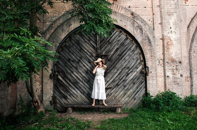 Woman standing on wooden wall
