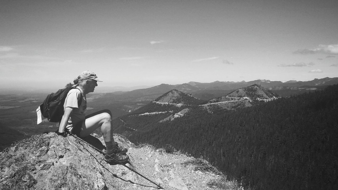 mountain, adventure, nature, real people, leisure activity, hiking, beauty in nature, sitting, one person, backpack, sky, full length, mountain range, lifestyles, scenics, outdoors, day, vacations, landscape, extreme sports, young adult, people