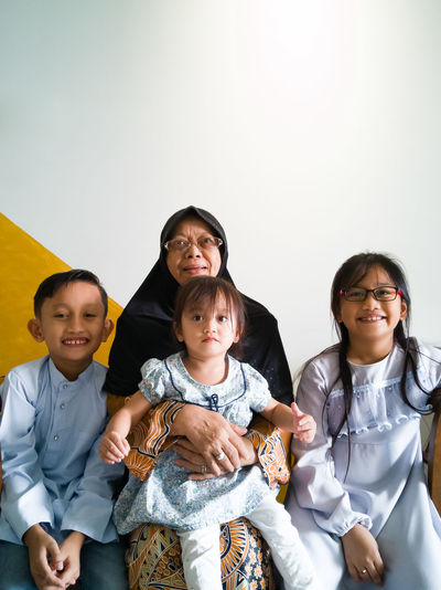 Portrait of cheerful grandmother sitting with grandchildren at home on eid-ul-fitr