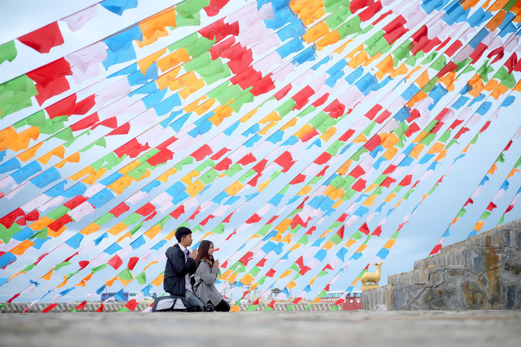 People praying while kneeling by colorful bunting against sky