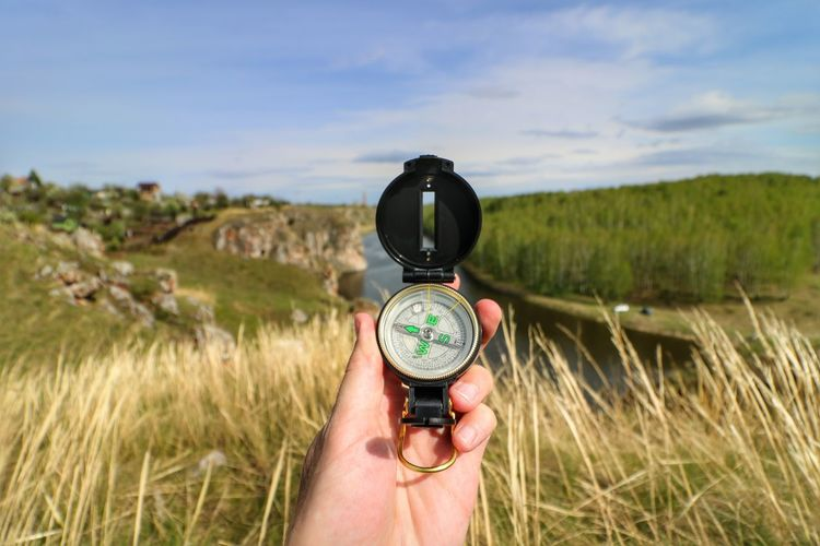 Cropped hand holding compass against field