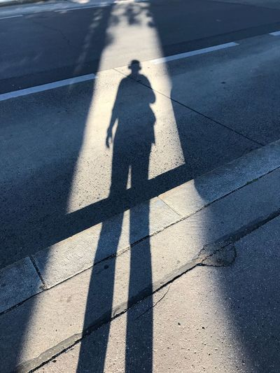 High angle view of person shadow on road