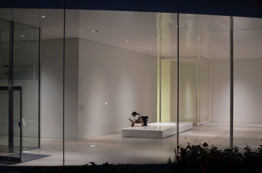 Looking in through tall glass windows at a person sitting alone in a museum with high blank walls. One Person Glass - Material Real People Illuminated Sitting Modern Architecture One Person Sitting Alone Japan Art Museum Outside Looking In Lonliness