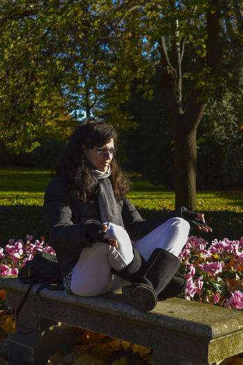 Beautiful Woman On Stone Bench In Park