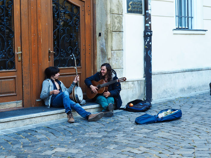 European Cities Real People Sitting Adult Casual Clothing Day Architecture Travel Destinations Travel Photography Street Photography Friends Daily Life European City Eastern Europe Cluj-Napoca Musical Instrument String Instrument Young Adult Guitar Young Men Musician Outdoors Entrance Built Structure Building Exterior Leisure Activity