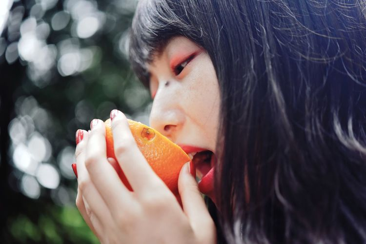 Close-up portrait of a woman eating food