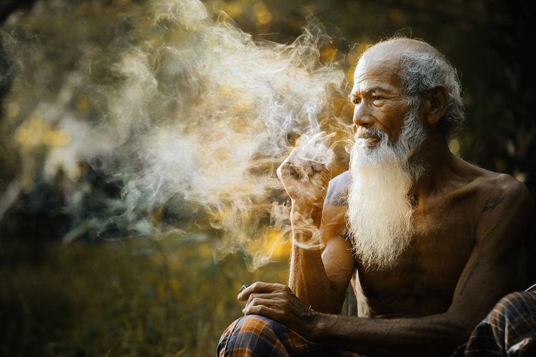 Senior man smoking while sitting outdoors