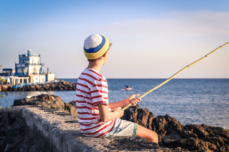 Boy fishing while sitting on rock at beach against sky