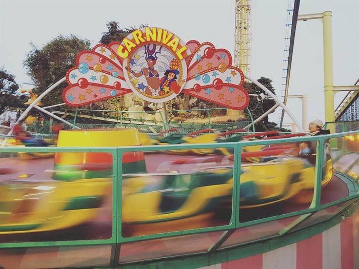 Multi colored carousel in amusement park against sky