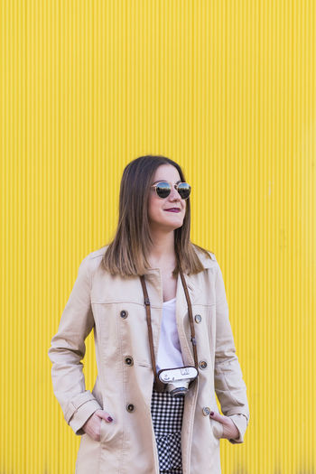 Fashionable young woman wearing sunglasses and overcoat while standing against yellow wall