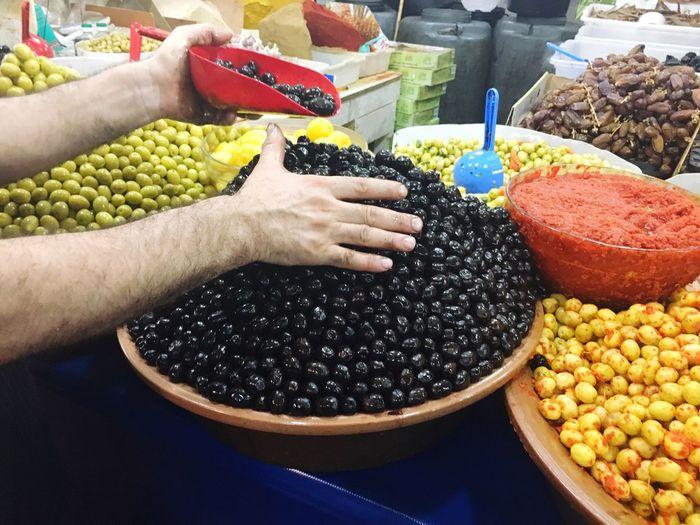 Cropped Hands Of Vendor Arranging Olives For Sale At Market Stall