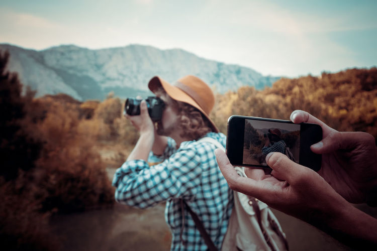 Man photographing with mobile phone against mountains