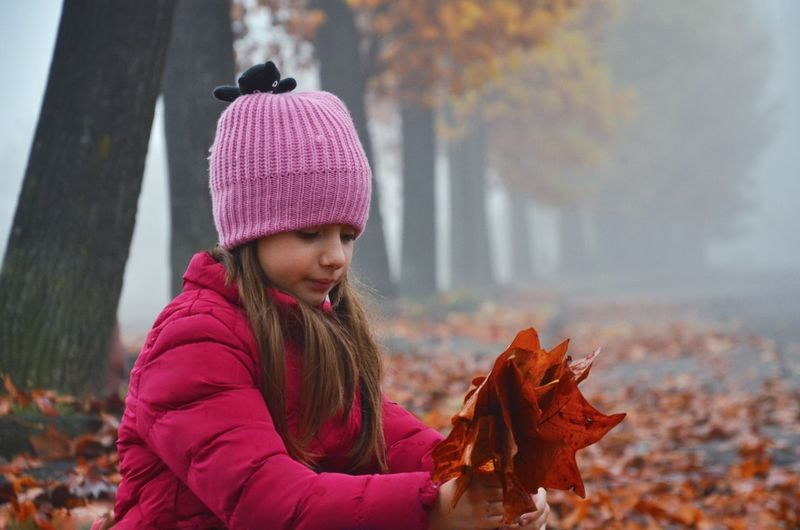 Girl holding autumn leaves