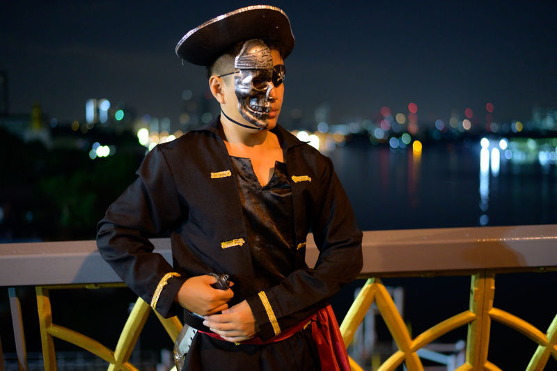 Young man wearing pirate costume standing on bridge against sky at night