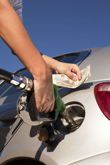 Cropped image of man refueling car while holding currency in hand