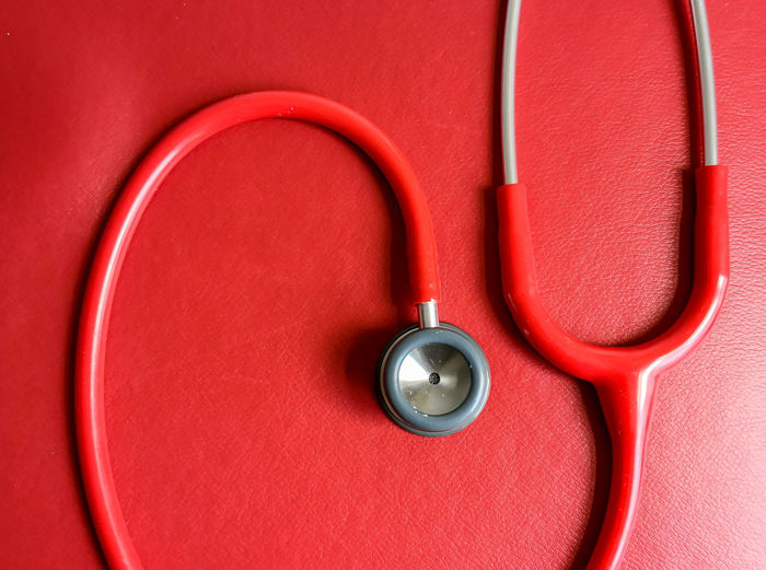 Red stethoscope on red bench at the doctor Biomedical Medicine Clinic Hospital Equipment Medical Equipment Examination Doctor  Red Healthcare And Medicine Directly Above Stethoscope  Backgrounds Full Frame Close-up