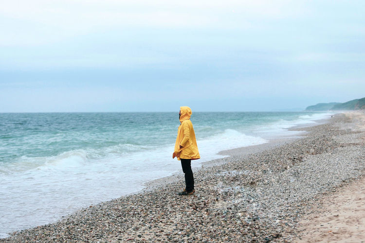 Side view of man wearing raincoat while standing at beach against sky