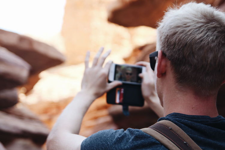 Rear view of man by rock formation taking selfie from mobile phone