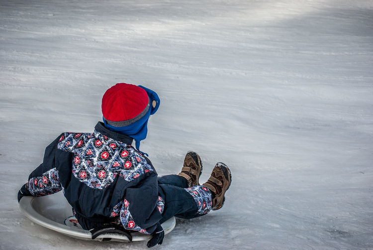 Rear view of boy tobogganing on snow covered field during winter