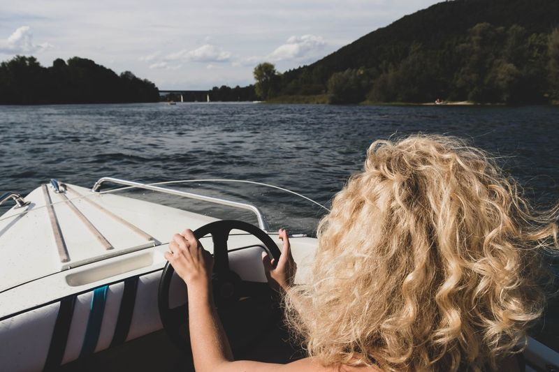 Woman in boat on lake against sky