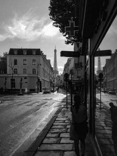 Woman walking on street amidst buildings in city
