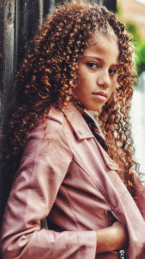 Portrait of girl with curly brown hair standing outdoors