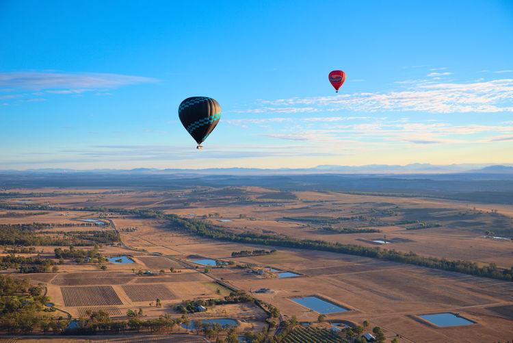 Hot air balloons flying over farm against blue sky