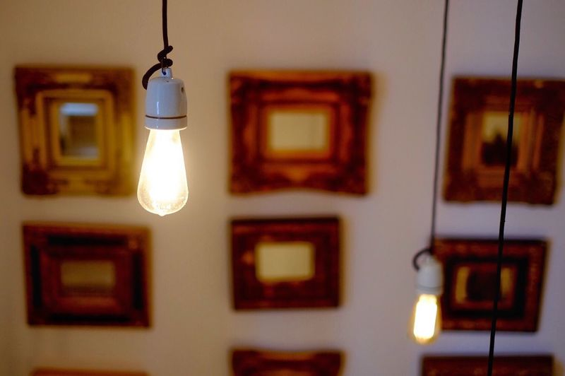 Close-up of illuminated electric bulb hanging at home