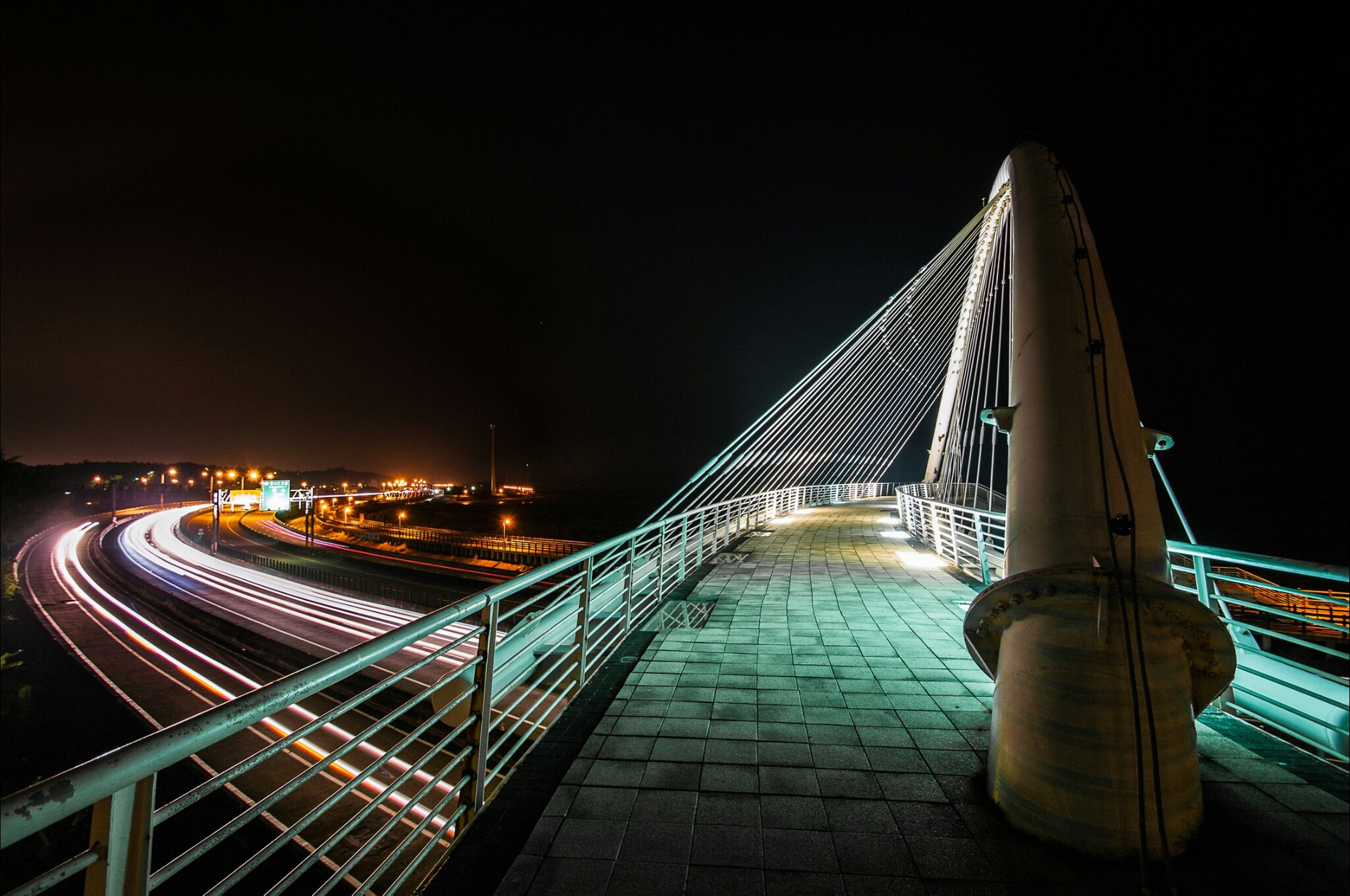 night, illuminated, architecture, built structure, bridge - man made structure, transportation, connection, clear sky, engineering, light trail, city, copy space, the way forward, travel destinations, suspension bridge, bridge, railing, travel, sky, building exterior