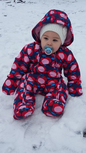 Full length of baby in warm clothing sitting on snow covered field
