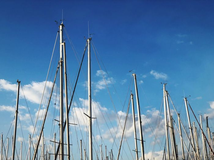 Low angle view of sail masts in blue sky