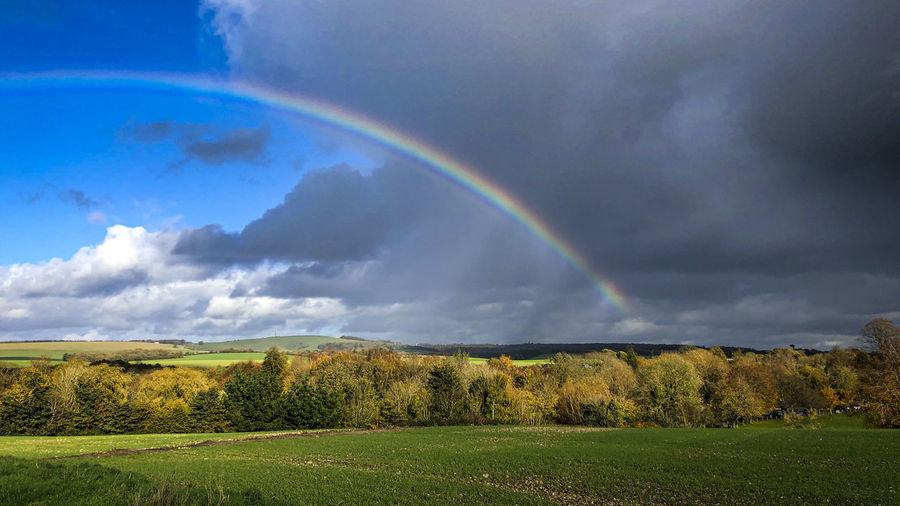 Scenic view of rainbow over field against sky