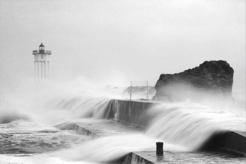 Waves Crashing On Rocks Near Lighthouse