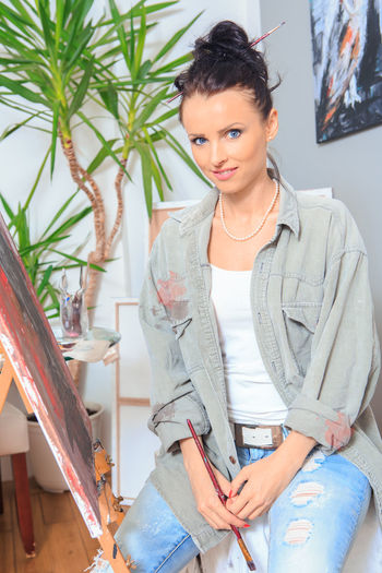 portrait of a female painter at work Adult Adult, Art, Artist, Artistic, Artwork, Beautiful, Brush, Canvas, Creative, Creativity, Drawing, Female, Girl, Hobby, Home, Interior, Lifestyle, Paint, Paintbrush, Painter, Painting, Palette, Person, Portrait, Professional, Studio, Woman, Work, Young Beautiful Woman Beauty Casual Clothing Creativity Front View Indoors  Leisure Activity Lifestyles Looking At Camera Occupation One Person Portrait Real People Smiling Three Quarter Length Women Young Adult Young Women