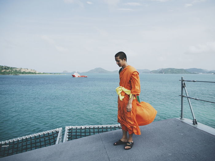 Side view of monk on boat deck sailing in sea