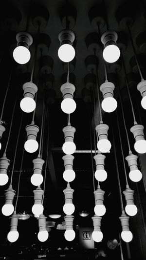 Low angle view of illuminated light bulb hanging against black background