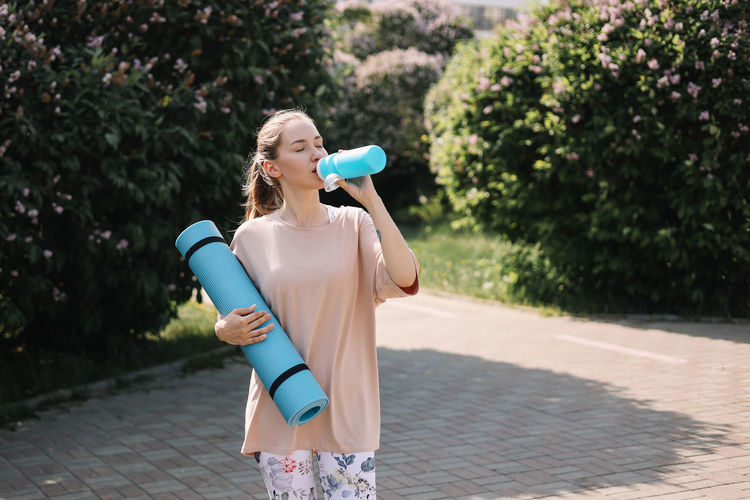 Athletic happy healthy young woman in sportswear goes after a sports workout exercise in nature
